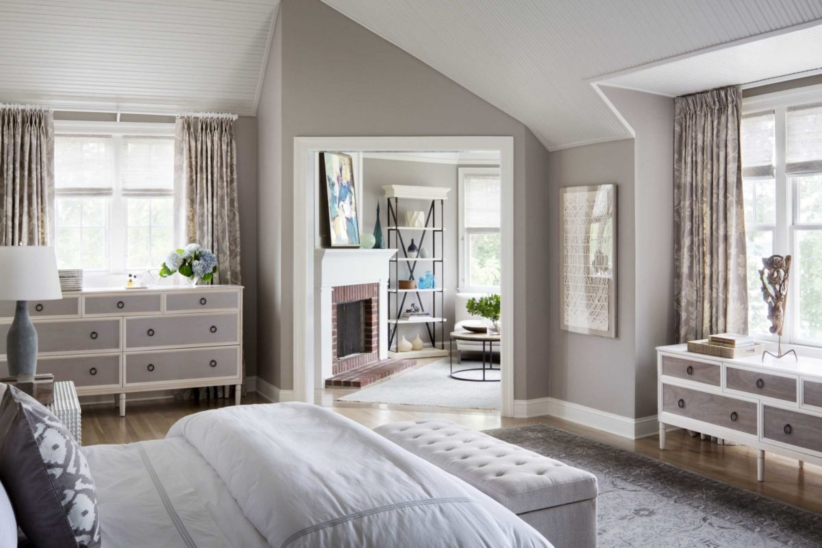 grey master bedroom with fluffy white bedding looking into sun room