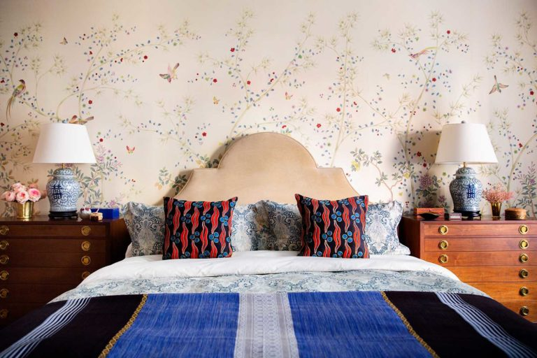floral wallpaper bedroom with cream headboard and red and blue bed