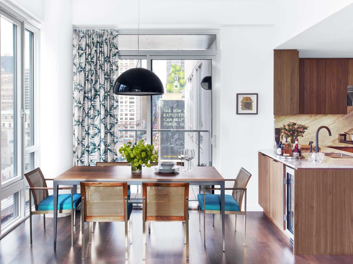 wood dining table with blue cushions overlooking Chelsea manhattan