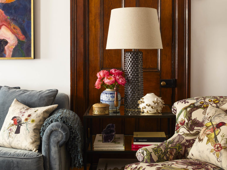 corner of vintage eclectic living room with silver lamp and floral chair