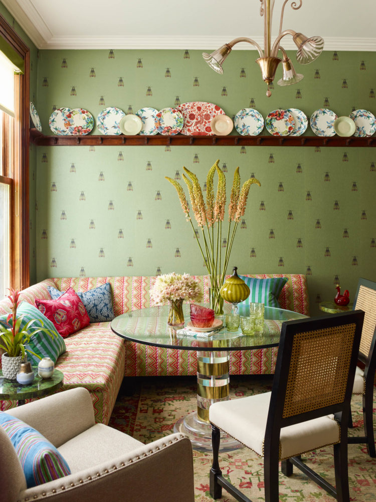 eclectic breakfast nook with green wallpaper and colorful seating and antique plates