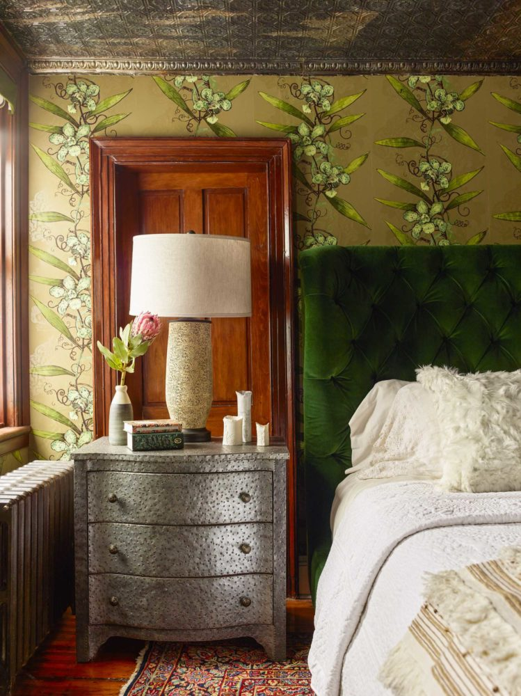 corner of bedroom with silver nightstand and green velvet headboard