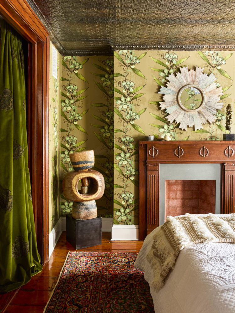 corner of bedroom with green velvet curtain and sculpture and fireplace