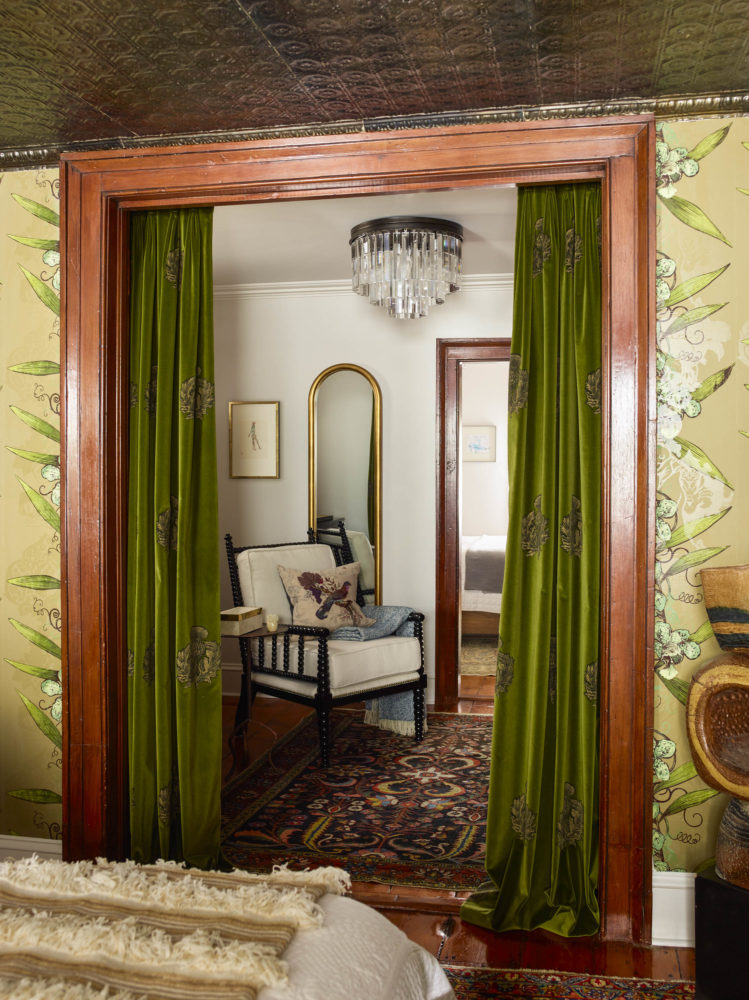green velvet curtains leading to vintage sitting room