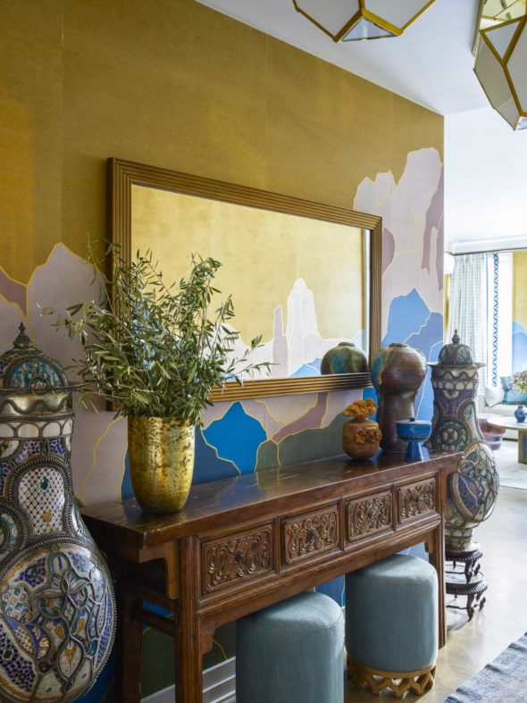 wooden entry table against yellow and blue wallpaper wall