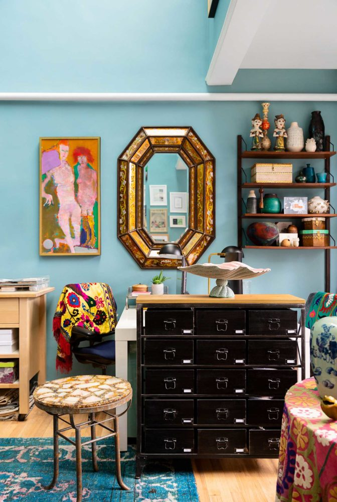 black storage cabinet and gold mirror against blue wall
