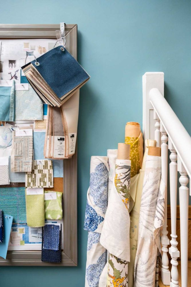 Blue interior design studio with rolls of fabric and inspiration board