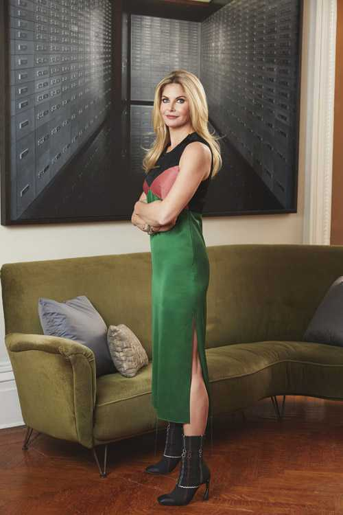 top nyc interior designer standing in front of olive green couch with green skirt and black top