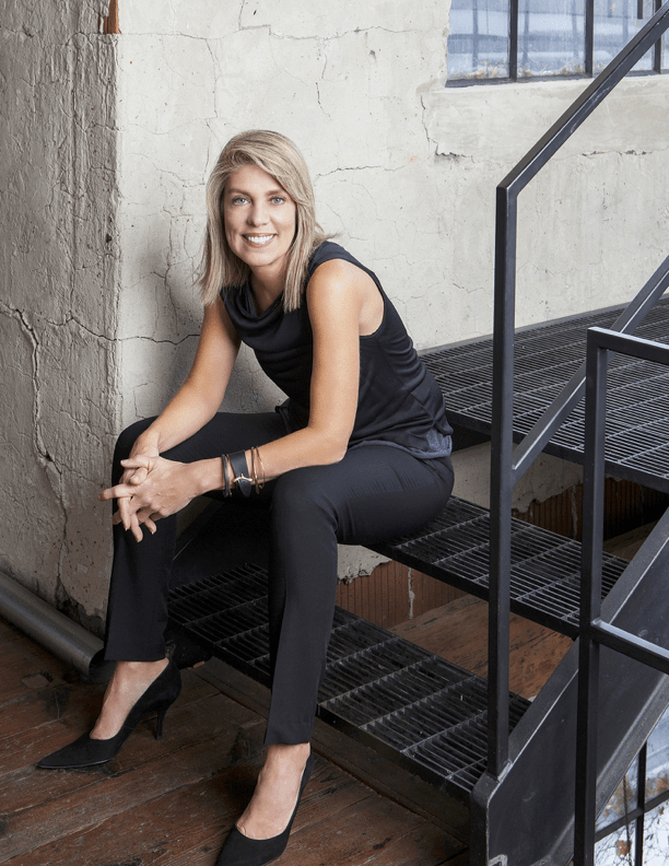 top nyc interior designer sitting on black steps in black outfit