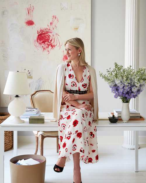 Top NYC Interior Designer sitting on white desk in red floral dress